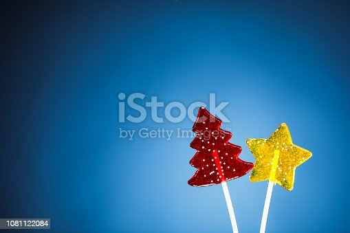 istock red Christmas tree and yellow star candy, blue background 1081122084