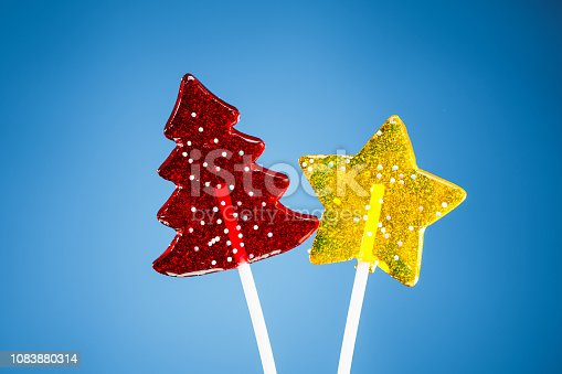 istock red Christmas tree and yellow star candy, blue background 1083880314