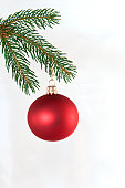 red Christmas tree ball on fir branch, against white background
