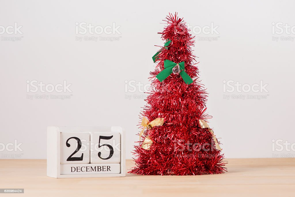 Red christmas tree on table with calendar 25 December stock photo