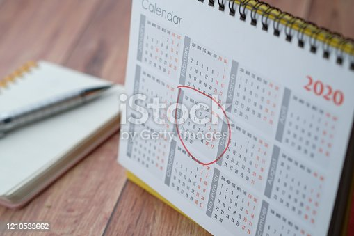 red circle on calendar date on table, close up.