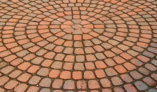 Red circular paved bricks with dirty moss stock photo
