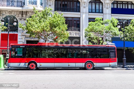 Side view of a red bus in a city street. Useful copy space available for text and/or logo in the bus side. DSRL outdoors photo taken with Canon EOS 5D Mk II and Canon EF 24-105mm f/4L IS USM Wide Angle Zoom Lens