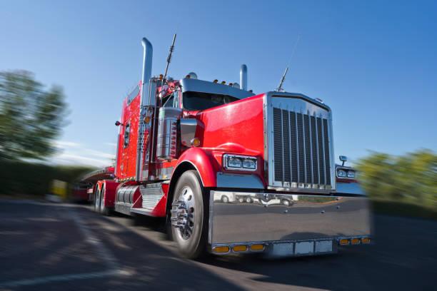 rote klassische big rig sattelschlepper mit viel chrom-accessoires mit semi-tieflader stehen auf raststätte - pickup trucks stock-fotos und bilder