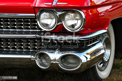 Two pairs of headlights and white wall tires of a shiny classic car
