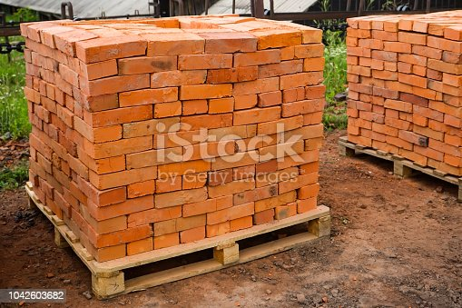 Red clay bricks are stacked on wooden pallets. Production of bricks from clay. Copy space