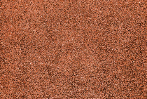 Red dry grungy clay tennis background texture.