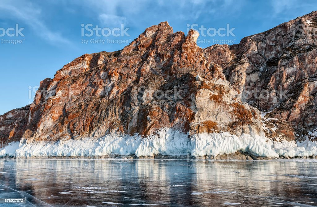 red cliff, bordered by white ice on lake Baikal stock photo