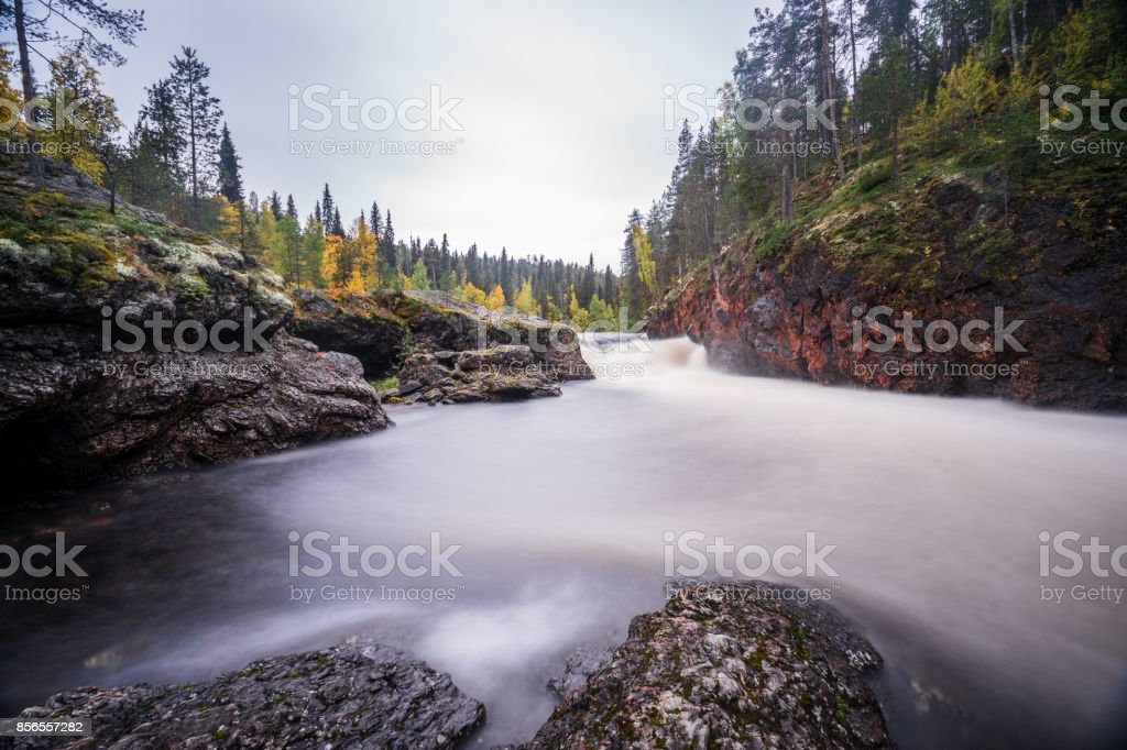 Red cliff, stone wall, forest, waterfall and wild river view in autumn. Fall colors - ruska time in Kiutaköngäs. One part of Karhunkierros Trail. Oulanka National Park, north Finland, Lapland, Europe stock photo