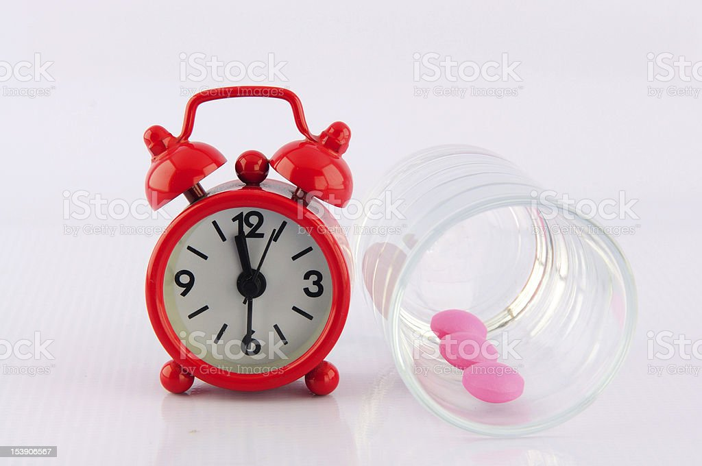 Red clock and pink tablet in dosage glass royalty-free stock photo
