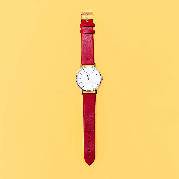 reloj rojo sobre fondo amarillo. minimalismo diseño - reloj de pulsera fotografías e imágenes de stock