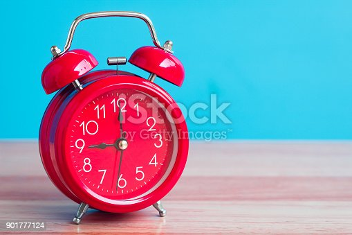istock Red clock placed on wooden table on blue background 901777124