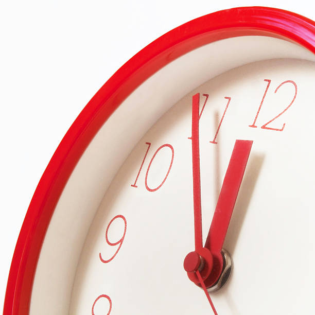 A red clock showing five minutes to midnight stock photo