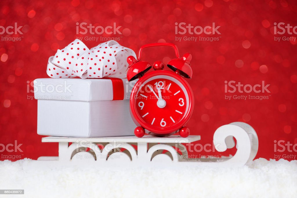 red clock with a gift box over sleigh in snow on red background stock photo