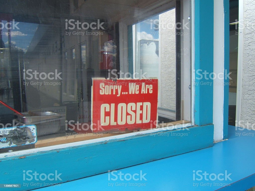 A red closed sign in the window of a blue building stock photo