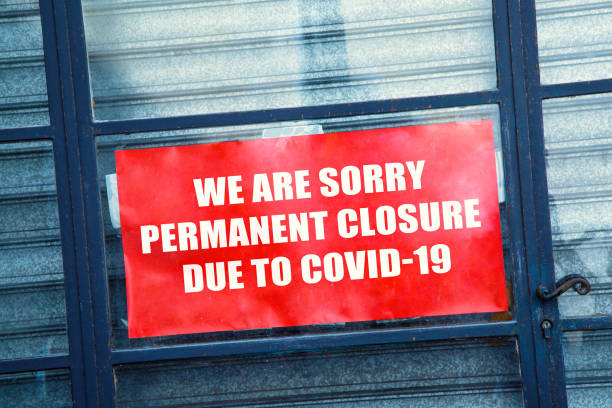 Red closed sign in the window of a shop displaying permanent closure stock photo