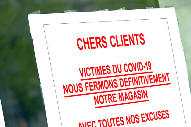 Red closed sign in the window of a shop displaying permanent closure in French language stock photo