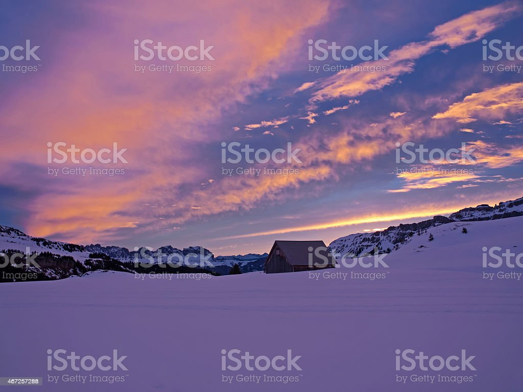 Red clouds over snowy alpine landscape at dawn stock photo