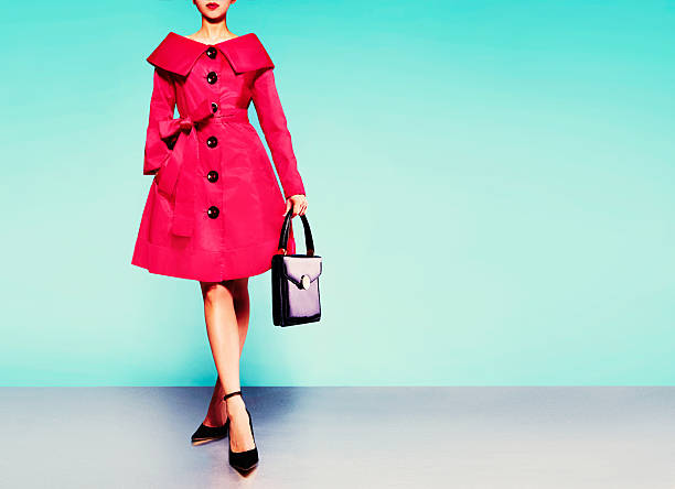 Red coat woman with black leather handbag with heels shoes. stock photo