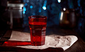 Red cocktail glass on krast paper. Blue blurred background. High quality photo