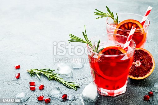 istock Red cocktail with blood orange and pomegranate. Refreshing summer drink on gray stone or concrete background. Holiday aperitif for Christmas party. 696382468
