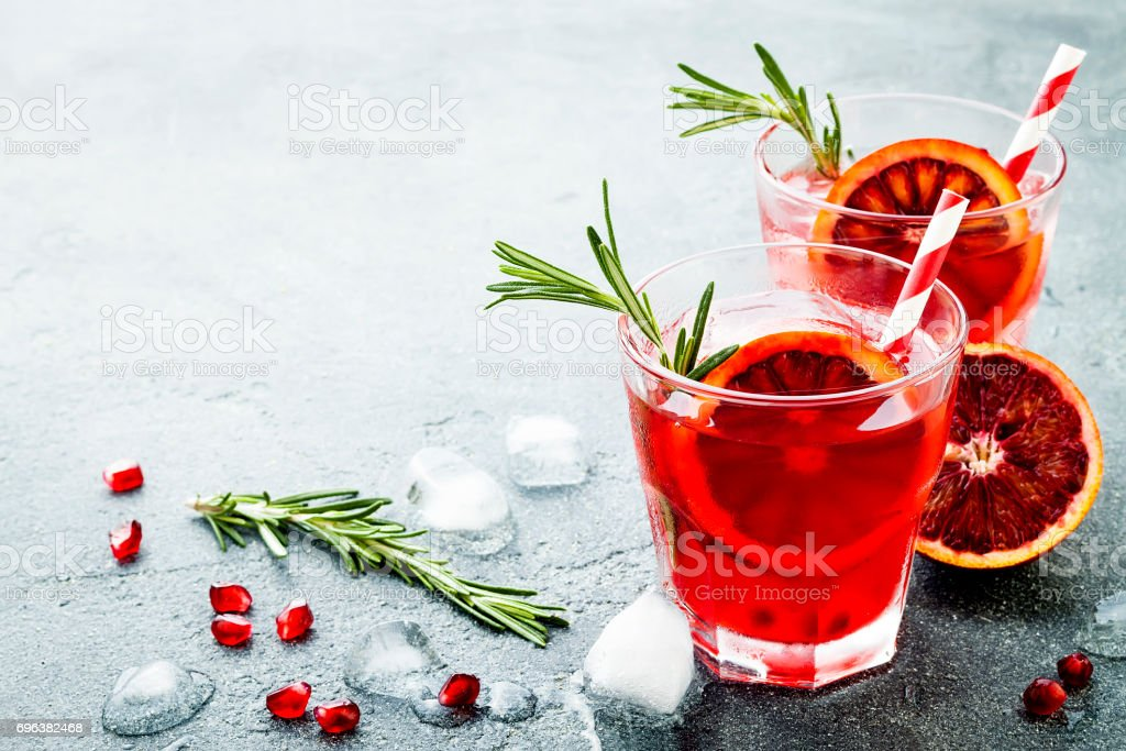 Red cocktail with blood orange and pomegranate. Refreshing summer drink on gray stone or concrete background. Holiday aperitif for Christmas party. - foto stock