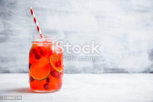 Red cocktail with cherry and lime in jar on the rustic background. Selective focus. Shallow depth of field.