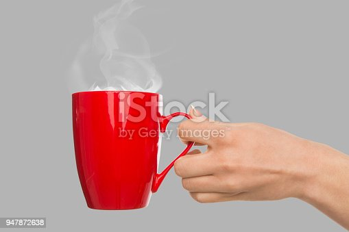 Female hand holding red cup with hot coffee at gray background, copy space