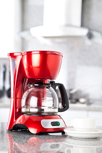 Red coffee maker on a grey marble countertop
