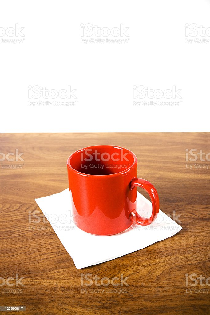 Red coffee mug and white napkin oak grained table  desk. royalty-free stock photo
