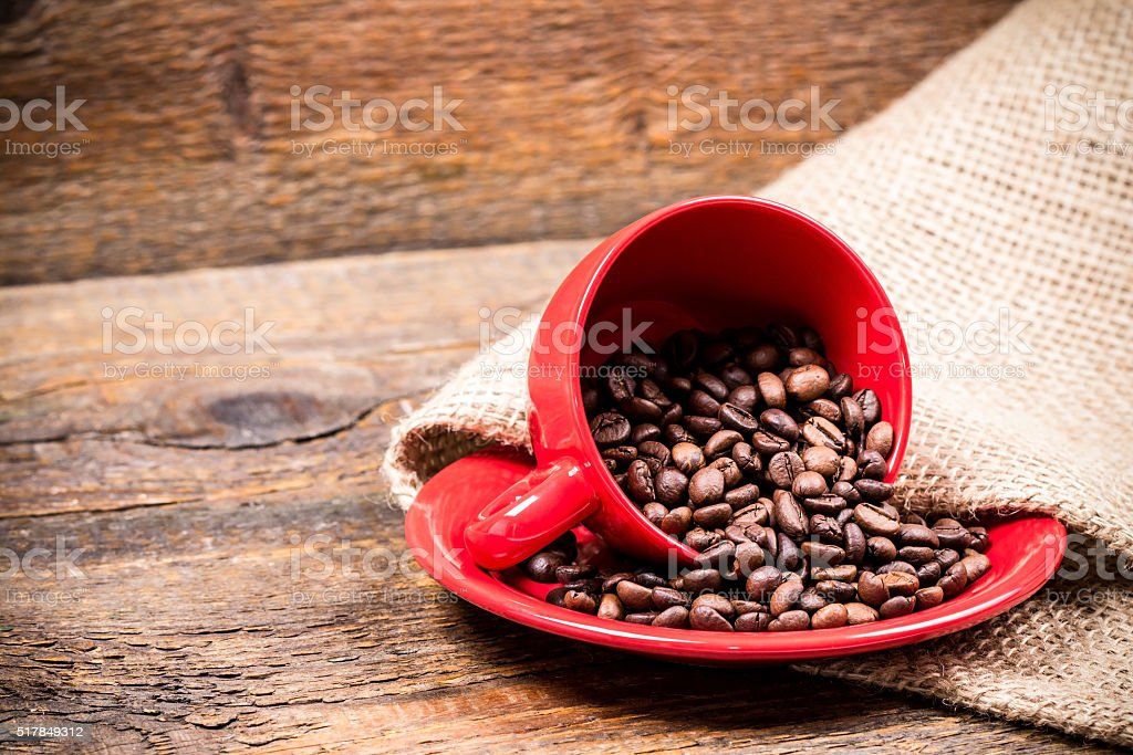 Red coffeecup and plate with spilled coffeebeans stock photo