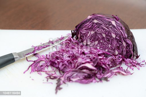 Red Coleslaw chopped on white and wooden background with kitchen knife on the side. Culinary top view