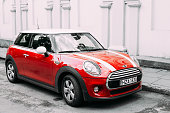 Red Color Car With White Stripes Mini Cooper Parked On Street In