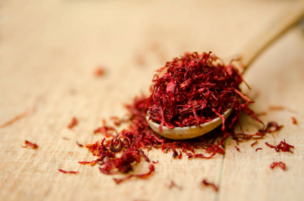 Red color Saffron in small wooden spoon on wooden table. Dull pestle of orchid flower. Red color Saffron in small wooden spoon on wooden table. Dull pestle of orchid flower. Close up view of natural exotic spice. saffron stock pictures, royalty-free photos & images