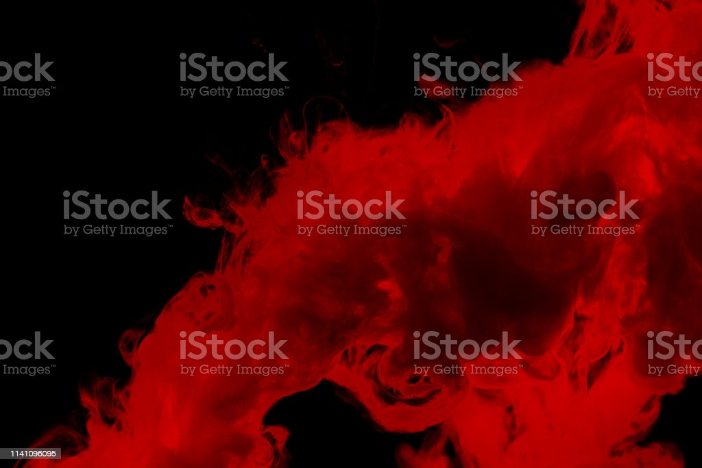 Red colored abstract acrylic paint spraiyng on a black background.