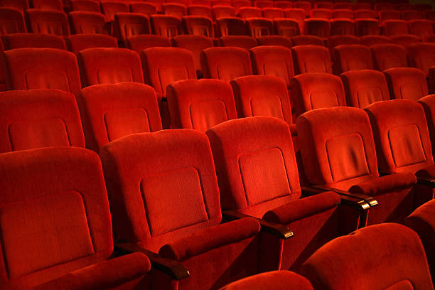 red colored empty movie theater chairs in row - seat stock photos and pictures