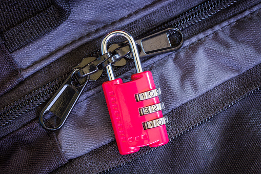 A little red combination padlock locking zippers on luggage
