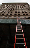 New York City, New York, USA. October 7, 2014. Red construction ladder leaning the building in Manhattan.