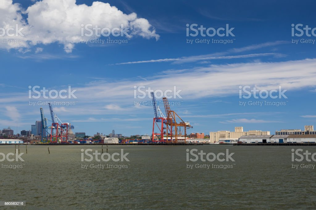 Red Container Cranes and Warehouses at Red Hook Port, Water of New York Harbor and Cloudy Blue Sky, Brooklyn, New York. stock photo