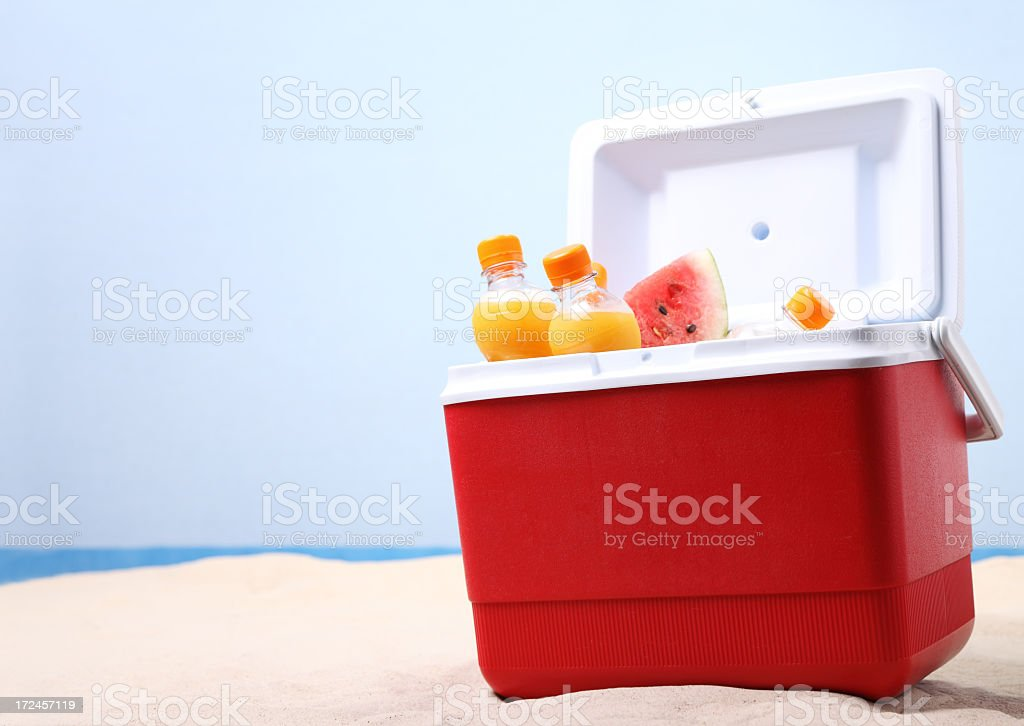 Red cooler full of fruit and juice on the beach royalty-free stock photo