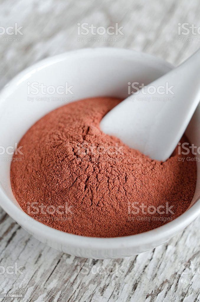 Red cosmetic clay powder in a small white bowl stock photo