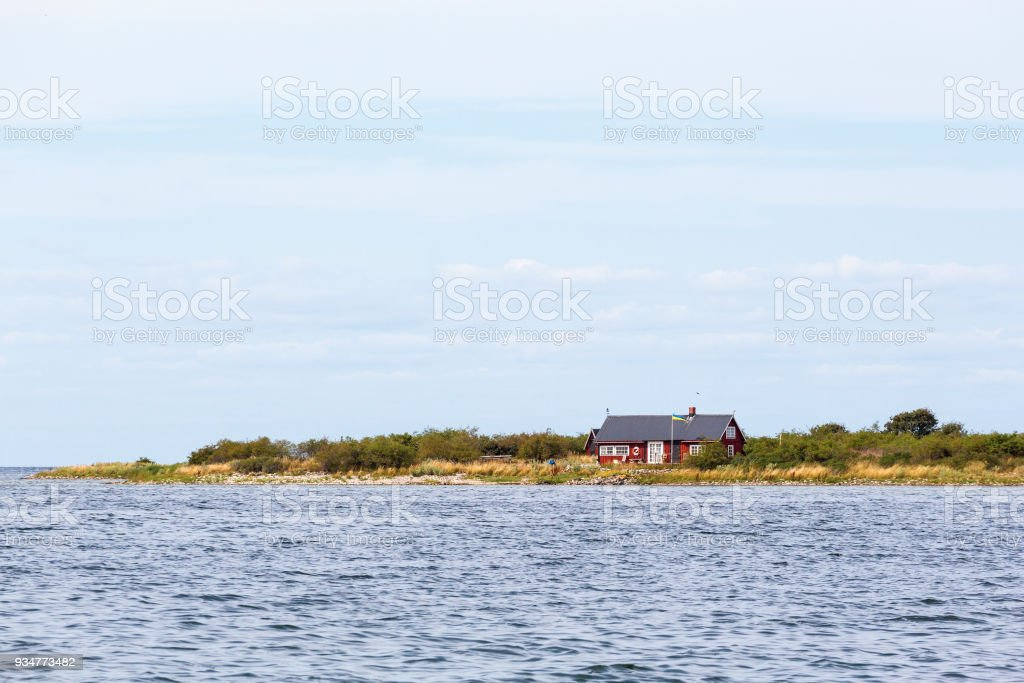 Red cottage at the beach stock photo