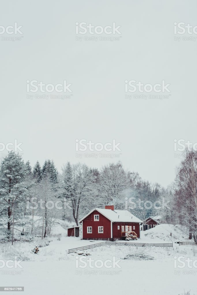 Red cottage house in rural winter snow landscape stock photo