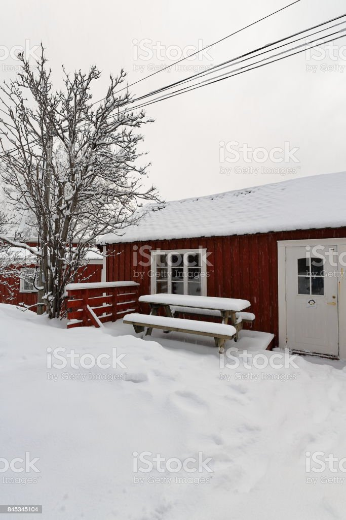 Red cottages-rorbuer under heavy snowfall in Hamnoy village. Reine-Moskenesoya-Nordland-Norway. 0381 stock photo