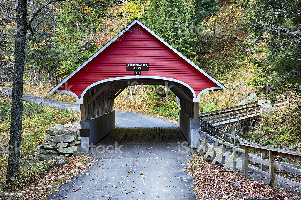 Red covered bridge in New Hampshire during Fall season stock photo