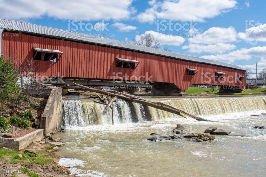 A red covered bridge spans a fall stock photo