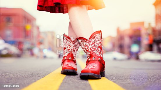 Road level view of red cowboy boots worn by a young woman in a red dress standing on the double yellow lines in the middle of the road in Nashville, Tennessee.