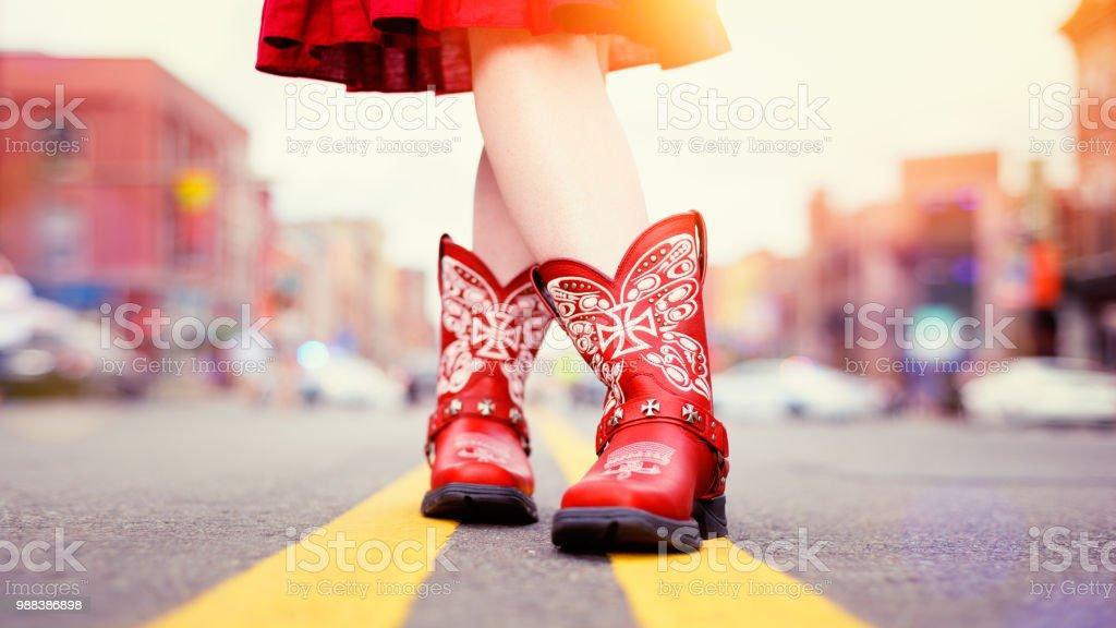Bottes de cow-boy rouge porté par Cowgirl en robe correspondant - Photo