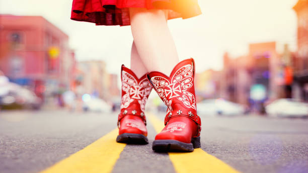 Red Cowboy Boots worn by Cowgirl in Matching Dress stock photo