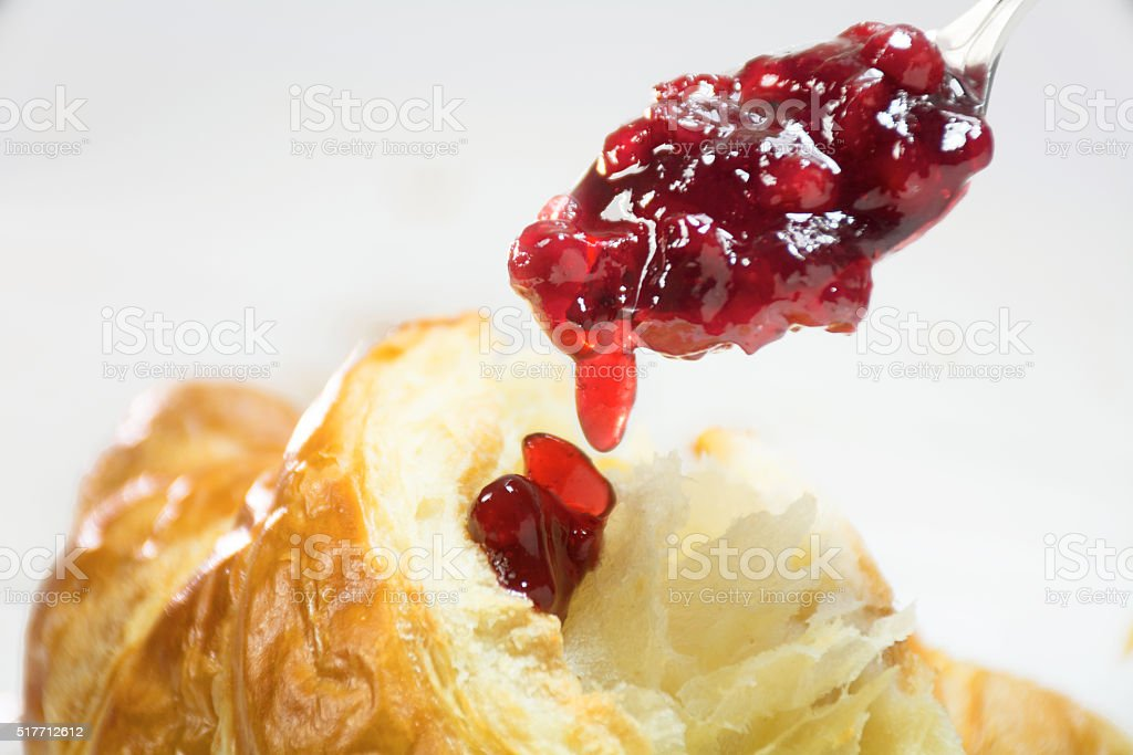 red cranberry jam dripping on a croissant, breakfast stock photo